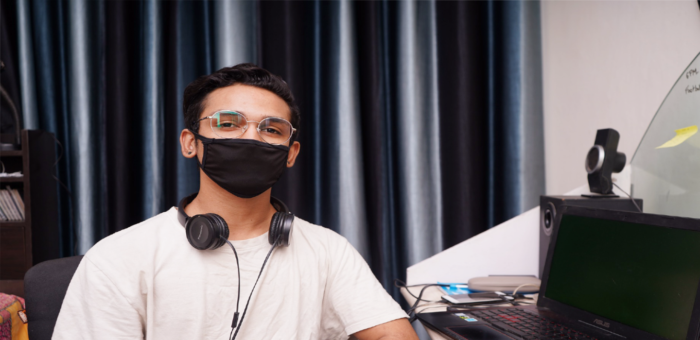 student with facial covering at home on computer