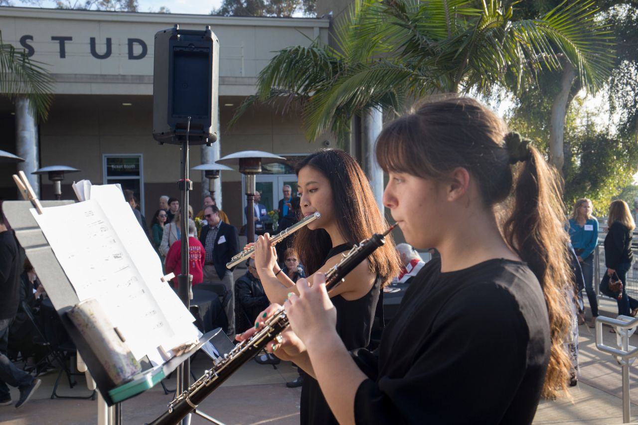 Music students play at a statue unveiling outside the performing arts center