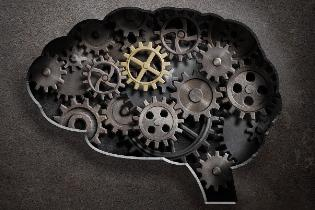 The silhouette of a human brain with cogs and gears filled in.