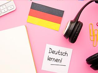 "The words ""Deutsch lernen!"" on a post it note on top of a desk."