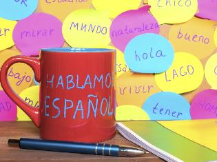 "A coffee mug on a desk that says ""Hablamos espanol""."
