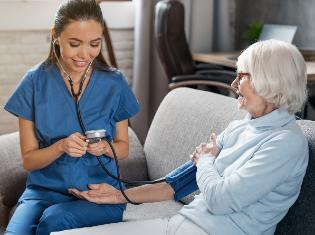 certified nursing assistant taking blood pressure on older woman