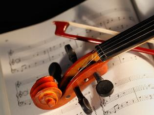A violin and bow laying on a sheet of music.