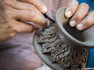 A person crafting a vase out of ceramics.