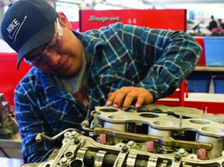 A student working on a car engine.