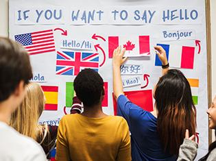 """If You Want to Say Hello"" written on a white board with several country flags and language translations."