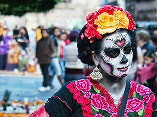 A person wearing day of the dead sugar skull make-up, a flower headband, and traditional spanish dress.