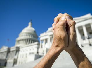 Two hands clasped together in front of a state capital building.